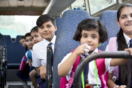 School children traveling in school bus looking at camera