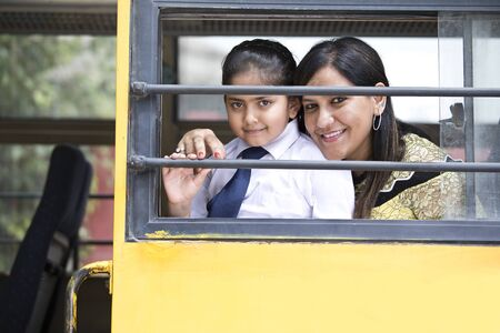 School teacher with schoolgirl looking through bus window