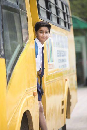 Indian schoolboy getting into the school bus