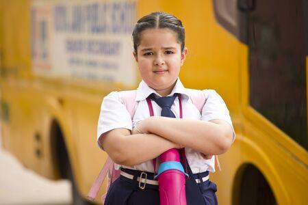 Portrait of schoolgirl in uniform with bag and water bottle