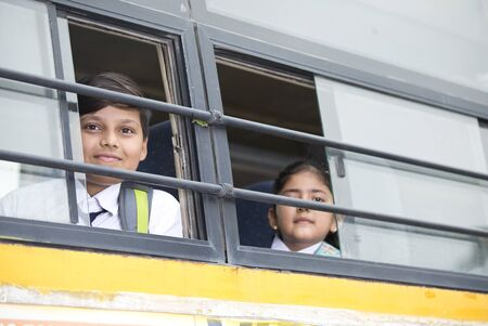 Happy school children looking from window of school bus