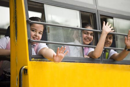 Happy school children waving hand from window of school bus