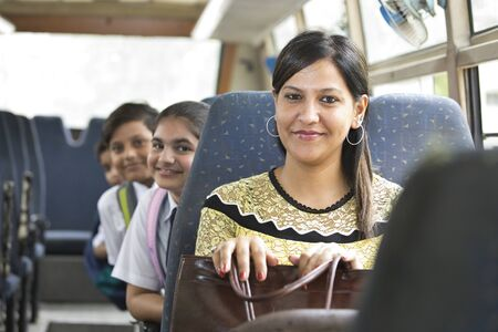 Happy teacher taking care of schoolgirl while traveling in school bus