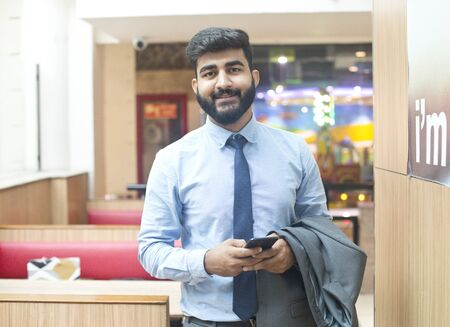 Young businessman holding mobile phone at cafeteria
