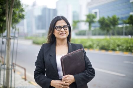 Young Indian businesswoman with a file in city 免版税图像 - 132288718
