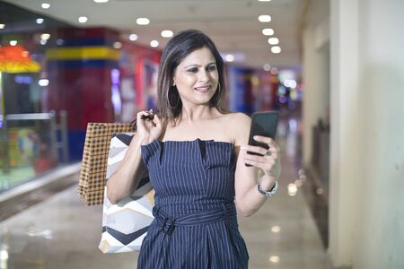 Stylish woman holding shopping bags and texting on mobile phone Stock Photo