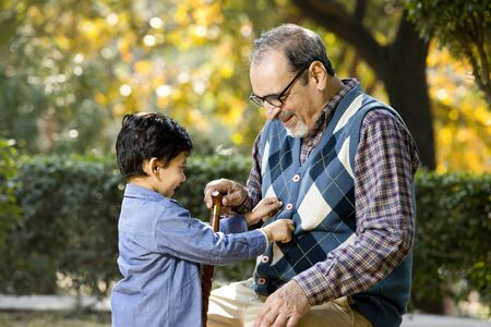 Grandfather with playful grandson at park