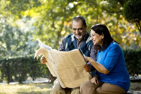 Happy senior couple reading newspaper outdoors at park