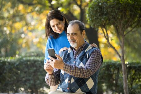 Senior woman sharing media content with her husband using mobile phone