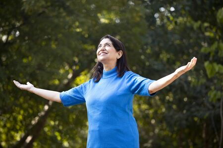 Senior woman with arms outstretched at park