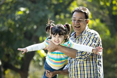 Cheerful father lifting daughter and helping her fly