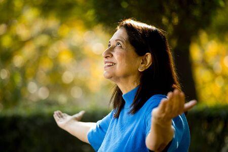 Mujer mayor, con, brazos extendidos, en, estacionamiento