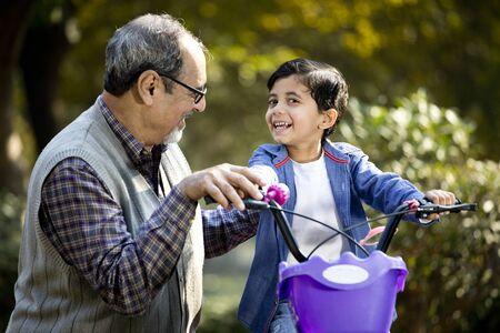 Großvater bringt seinem Enkel das Radfahren im Park bei