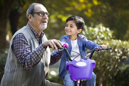 Grandfather teaching his grandson cycling at park
