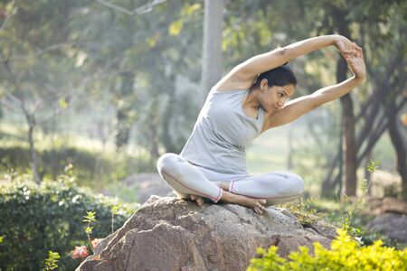 Woman in sportswear doing yoga and stretching at park