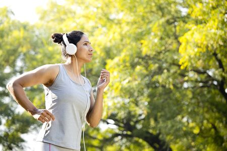 Sportswoman listening music and jogging at park
