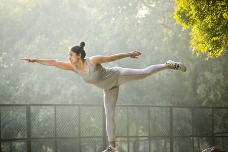 Woman standing on one leg and doing stretching exercise at park