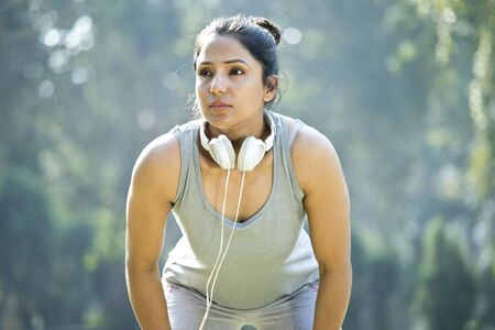 Fit woman in sportswear listening music on headphones at park outdoor