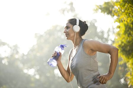 Woman in sportswear listening music while exercising at park outdoor