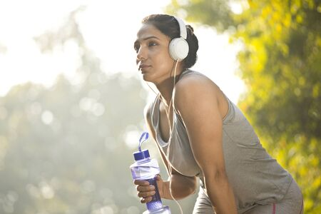 Fit woman with dumbbell shape water bottle and headphones at park Stock fotó