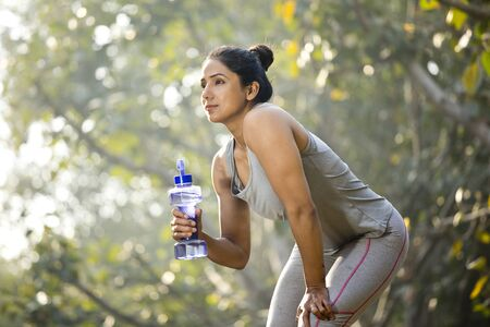 Fit woman with dumbbell shape water bottle at park