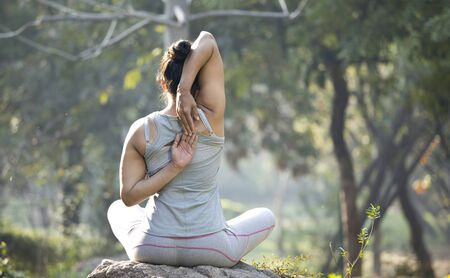 Woman in sportswear doing yoga and stretching at park outdoor Stock Photo