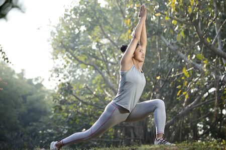 Woman in sportswear practicing yoga tree pose at park