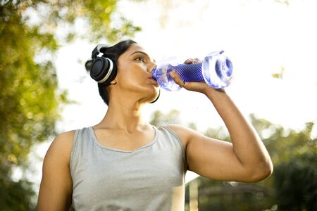 Sportswoman drinking water and listening music at park
