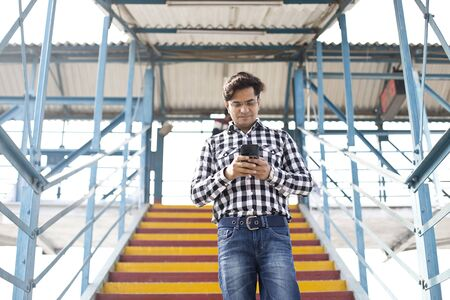 Young man using mobile phone while walking in stairs