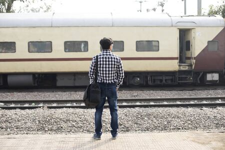 Man with holding bag waiting at railroad station platform Stock fotó