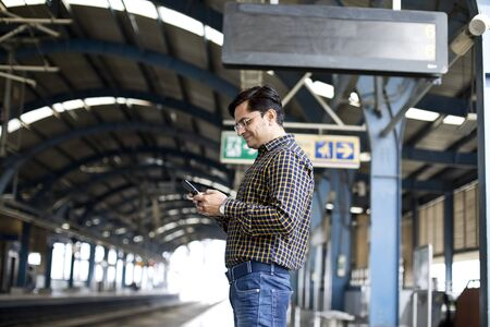 Man using mobile phone at railroad station platform Stock fotó