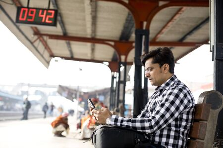 Man using phone while waiting at railroad station platform