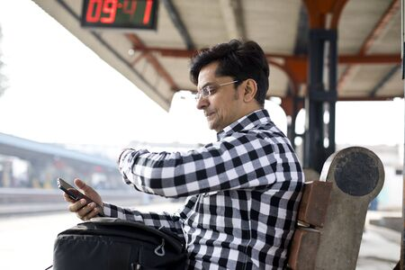 Man checking time while waiting at railway station