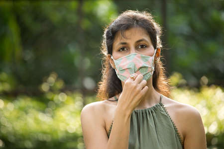 Woman adjusting protective face mask at park Stock fotó