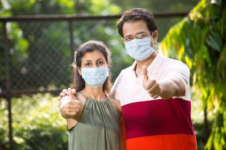 Couple with protective face mask at park