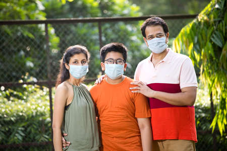 Family with protective face mask at park