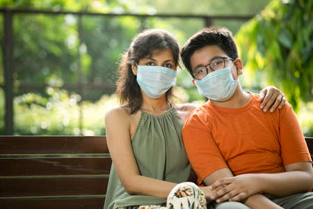 Mother and son with protective face mask relaxing on park bench