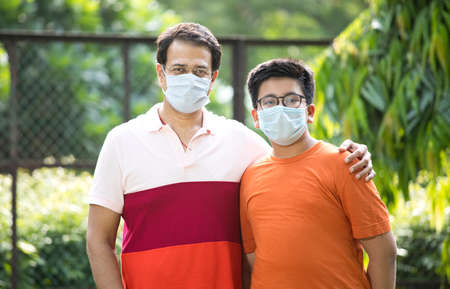 Father and son with protective face mask looking at camera