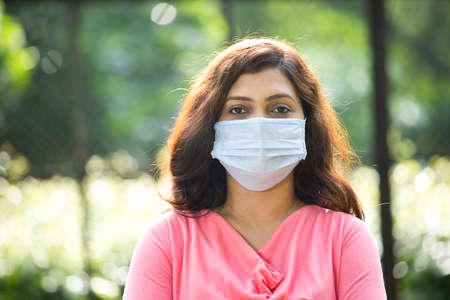 Woman with protective face mask at park