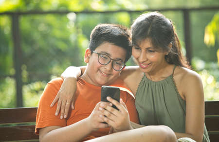 Mother with son on a video call using mobile phone at park