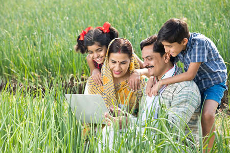 Rural family using digital tablet on agriculture field Foto de archivo