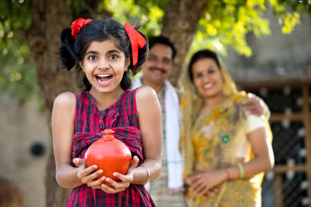 Rural Indian family with surprised daughter holding piggy bank Standard-Bild