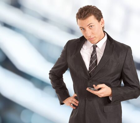 Young attractive businessman writing a text message. Blurred background. Stock Photo - 9013396