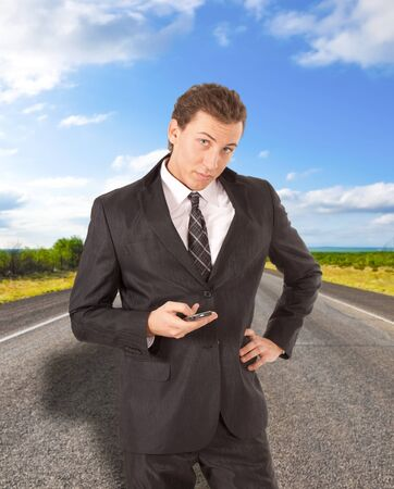 Young businessman requesting assistance on a desert road. Stock Photo - 9013627