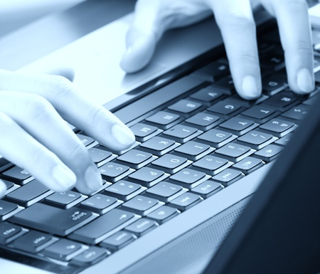 Hands typing on a notebook keyboard. Blue toned. Stock Photo - 9013296