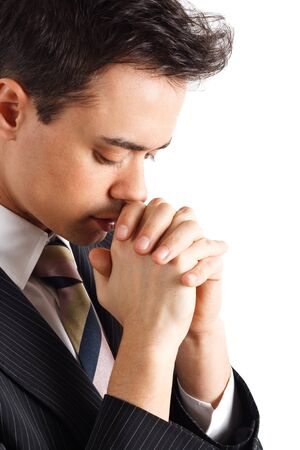 praying people: Young businessman praying. Isolated against white background.
