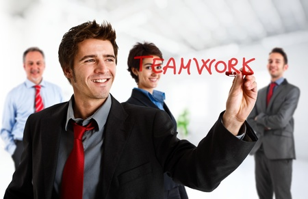 Friendly businessman writing the word Teamwork on the screen photo