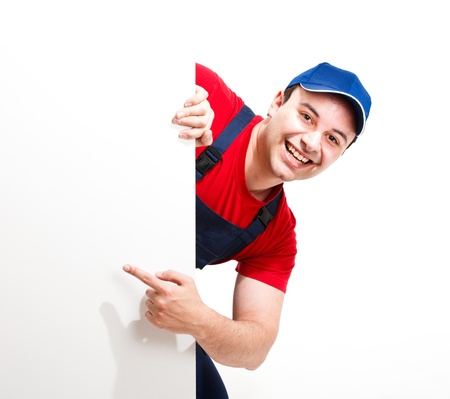 painters: Portrait of a friendly worker pointing his finger to a blank board
