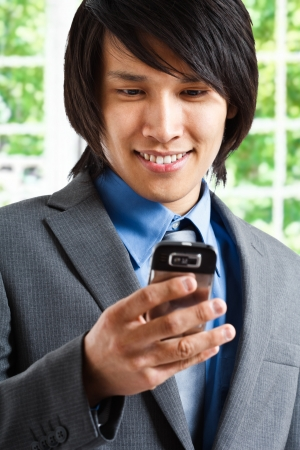 Oriental businessman reading an email on his smartphone Stock Photo - 13945425