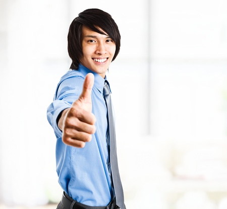 Portrait of an handsome oriental businessman giving thumbs up Stock Photo - 13945245